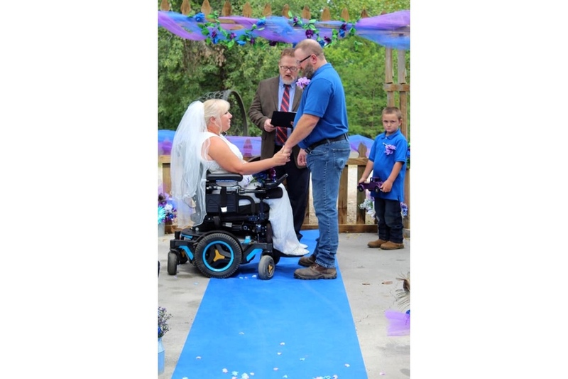 image is a photo of AMM Minister Andrew (Andy) Brasfield performing the wedding ceremony for his son Matt and daughter-in-law Shannon, the couple are holding hands at the altar and Shannon is wearing a white wedding dress and sitting in a wheelchair while Matt wears a blue shirt and clasps her hands