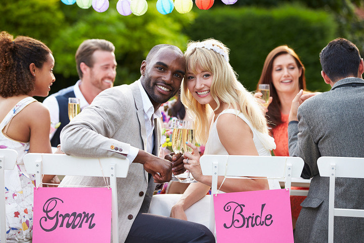 image is a photograph of a bride and groom smiling with their faces close together, they are holding champagne flutes and sitting with friends outdoors at a large table, with signs and lanterns hanging to show that it is their wedding ceremony