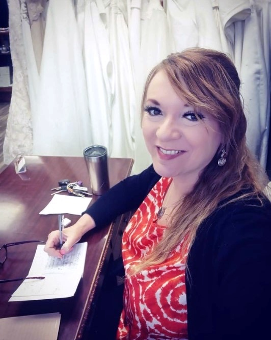 Donna Norris poses at her desk while working on a wedding ceremony script, beautiful white wedding dresses hang behind her in the background