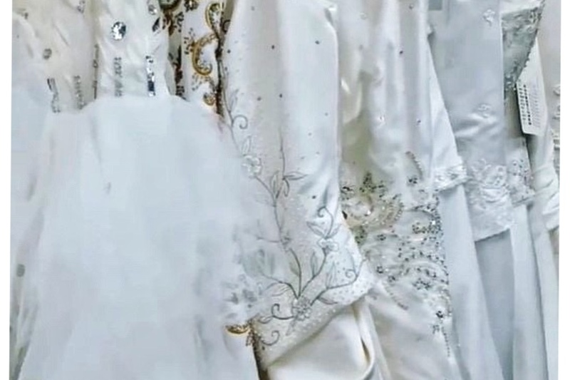 Image is a photograph of decorative white wedding dresses in the Off the Beaten Path Micro Chapel in Eastern TN