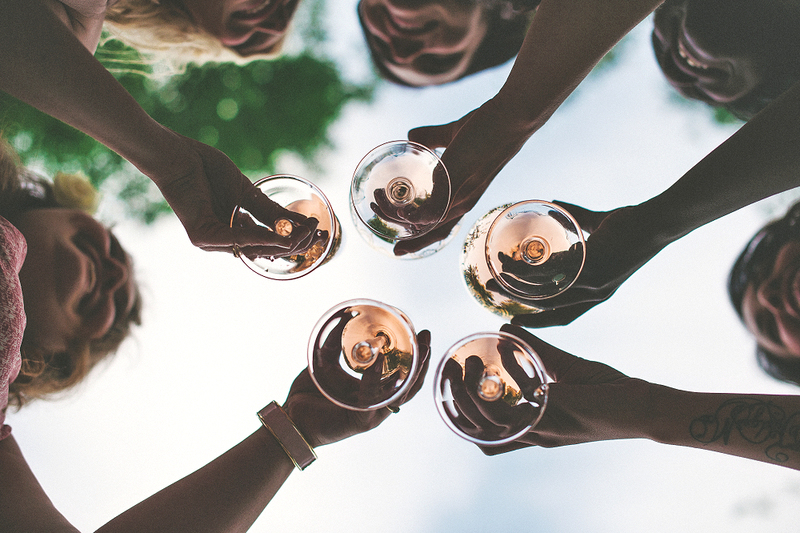 Image is a photograph of several woman toasting at a wedding, taken from below, looking up through their outstretched hands, there are green tree leaves above