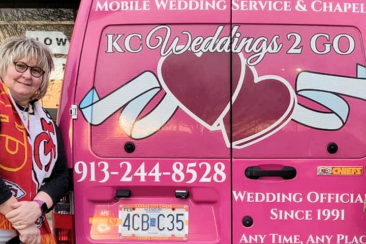 Image is a photograph of Pastor Nancy Kerr of Kansas City standing next to her pink mobile wedding officiant van as she drives to the Super Bowl to officiate weddings for Chiefs fans