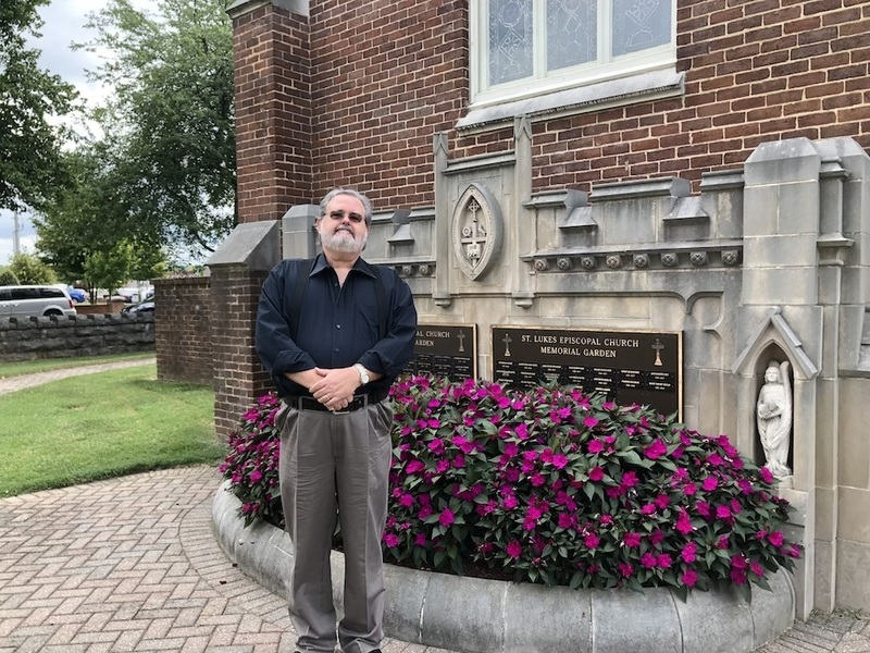 Image is a photograph of AMM Minister and wedding officiant Timothy (Tim) Hooker standing with his hands crossed in front of him, smiling, outside in front of a brick building with flowers planted, there are trees behind him and it's a sunny day