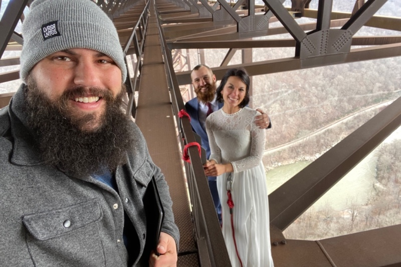 Image is a selfie taken by AMM Minister and professional wedding officiant Mathew Anderson performing an elopement ceremony on the New River Gorge Bridge, the couple and officiant smile at the camera with the bridge and river spanning the background