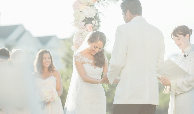 image is a brightly lit photo of an outdoor wedding between a young man and woman, being officiated by the officiant, IAPWO President Reverend Laura C. Cannon, who is holding a decorative book and reading a portion of the wedding script