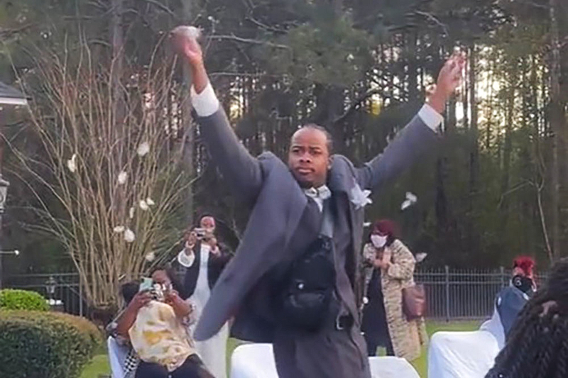 A man dances down a wedding aisle in a sharp looking gray suit, tossing petals from a leather fanny pack