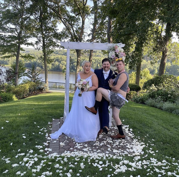 The happy couple with their flower dude pose under the wedding arch, surrounded by white petals and green grass. The flower dude has his leg up in a funny pose