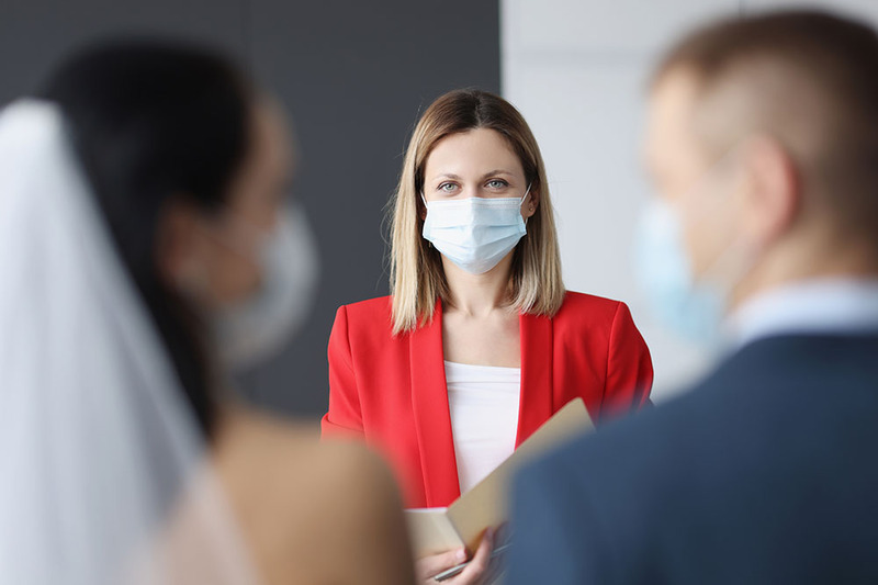A wedding officiant wears a mask while officiating a ceremony, the photo is taken from behind the couple. The officiant wears a red jacket and her eyes show she is smiling behind the mask.