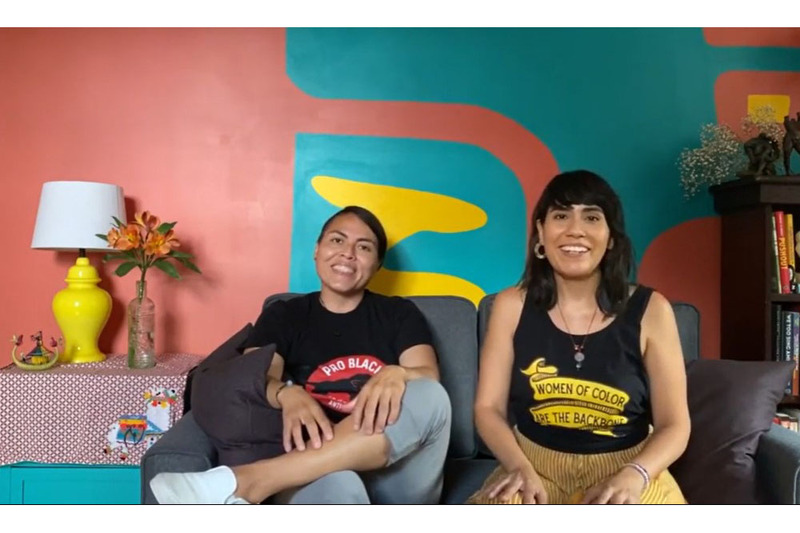 """A photo of Karla and Daniela of Once Upon a Vow taken from their """"about us"""" video. Karla is on the left, with her hair pulled back, wearing a black shirt with lettering that is partially obscured, that begins, """"pro black"""" and smiling. Daniela is wearing a black tank top, with the lettering """"women of color are the backbone..."""" and yellow pants. She is smiling. The room is painted and decorated in vibrant bright colors."""