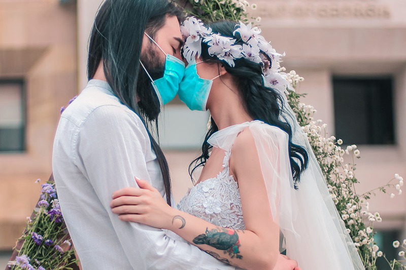 A young couple embrace during their wedding ceremony while wearing blue surgical masks. They both have long dark hair and are wearing white, and their foreheads rest together.