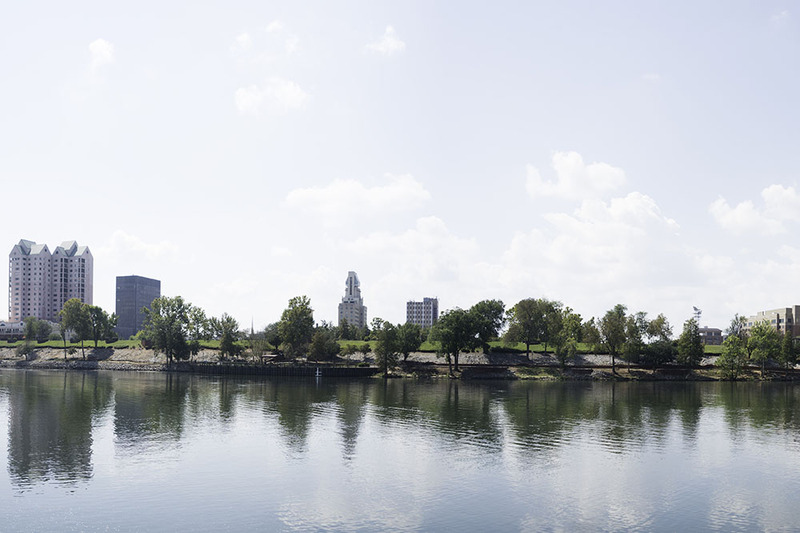 Photo shows Augusta Georgia, taken from across the river on a bright sunny day.  The shore is lined with trees, and there are large city buildings in the background.