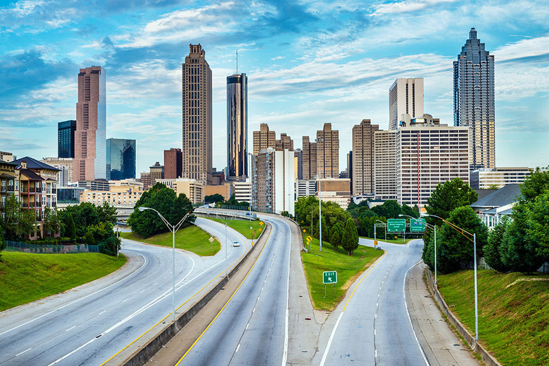 Photo shows the Atlanta skyline in vivid colors, with a blue sky and lots of white clouds moving behind the buildings. Atlanta is in Fulton County, Georgia - where to get a marriage license in Fulton County!