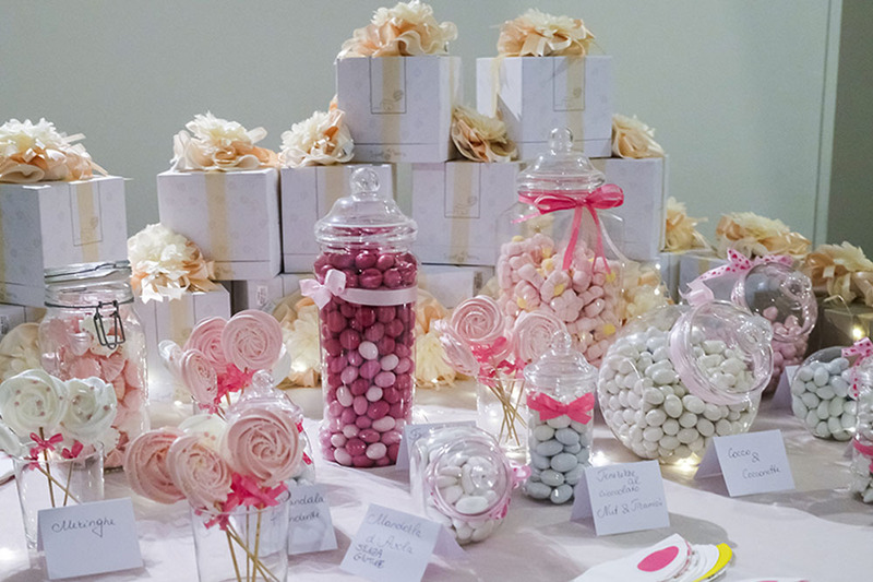 Photo shows a table of Italian wedding confetti candies, a confettata, with pink and white color scheme