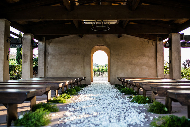 A photograph of a wedding venue villa at a winery, with white flower petals leading the way to the wedding altar in an Italian tradition