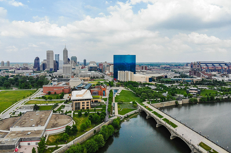 Photo of the Indianapolis Indiana skyline, with city buildings, a bridge and a river, and a blue sky with white clouds