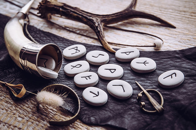 Photo shows Norse runes and a ceremonial Viking horn, with other tools for witchcraft and Pagan spell casting
