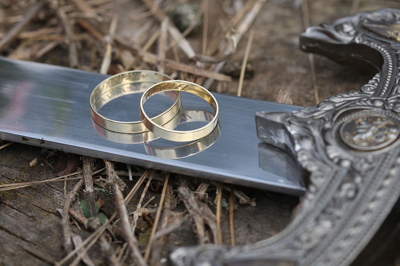 Photograph shows a close up of wedding rings engraved with Norse runes placed on the blade of a Viking wedding sword