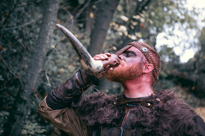 A Viking in a helmet with horns and rustic leather medieval dress stands in the woods drinking mead from an animal horn carved into a cup.