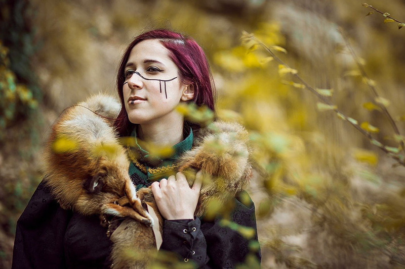 A young Viking Pagan woman dressed in a fur collared coat standings looking into the distance, surrounded by trees. Her hair is a bright dyed magenta and hangs loose and long, and she has decorative face paint across her cheeks in a black line