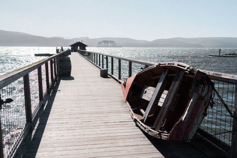 Photo of the beautiful Nick's Cove on Tomales Bay, with a dock stretching out into the water, a scenic backdrop for the couple's a wedding reception