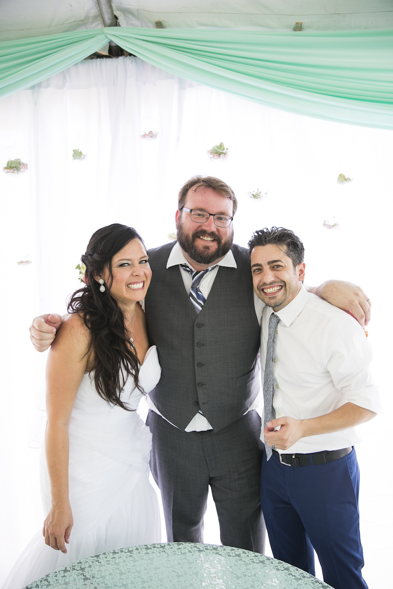 A photo of a newly married couple and their wedding officiant Matt McMurphy smiling and enjoying themselves against a white background with flowers and teal fabric banners, photo by Jeannie Mutrais