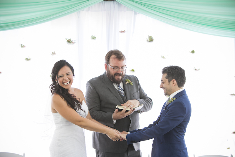 A candid image of the wedding with the couple and their wedding officiant laughing and enjoying themselves against a white background with flowers and teal fabric banners, photo by Jeannie Mutrais
