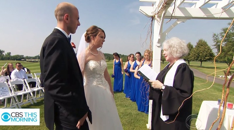 Image is a photograph of an AMM Minister Florence Hunt marrying a young couple outdoors, there is a clear blue sky behind them and everyone looks happy