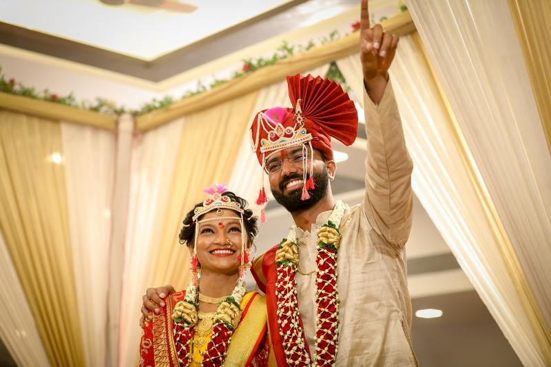Image is of a newly married couple waving happily to the the camera after the ceremony