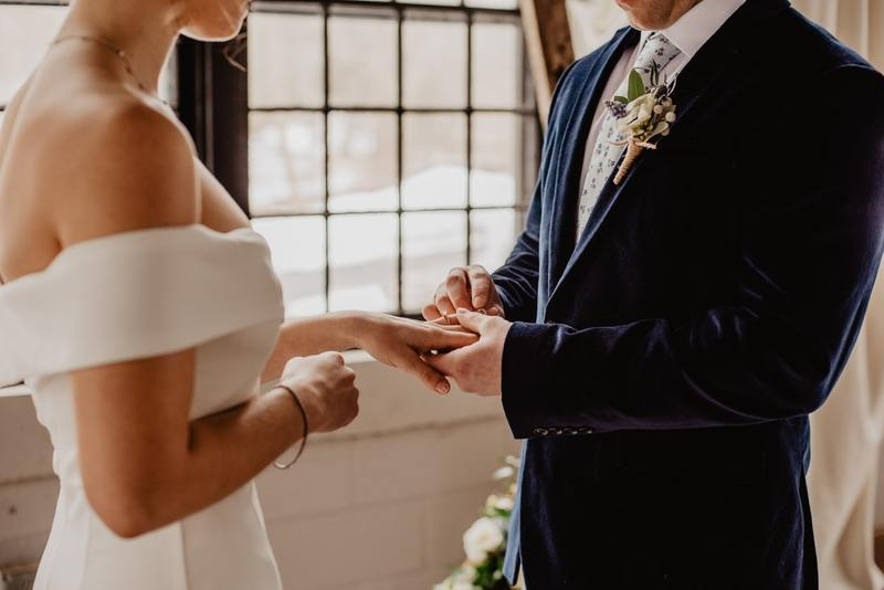 A photograph of a man and woman in a wedding dress and suit in front of a large window, the man is putting a ring on the woman's hand as part of the ring exchange