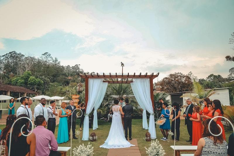Image is of a young couple surrounded by friends and family as they say their vows at a wedding ceremony, they stand in front of a wedding arch draped with white flowing fabric, outdoors, with lush green trees behind the ceremony space