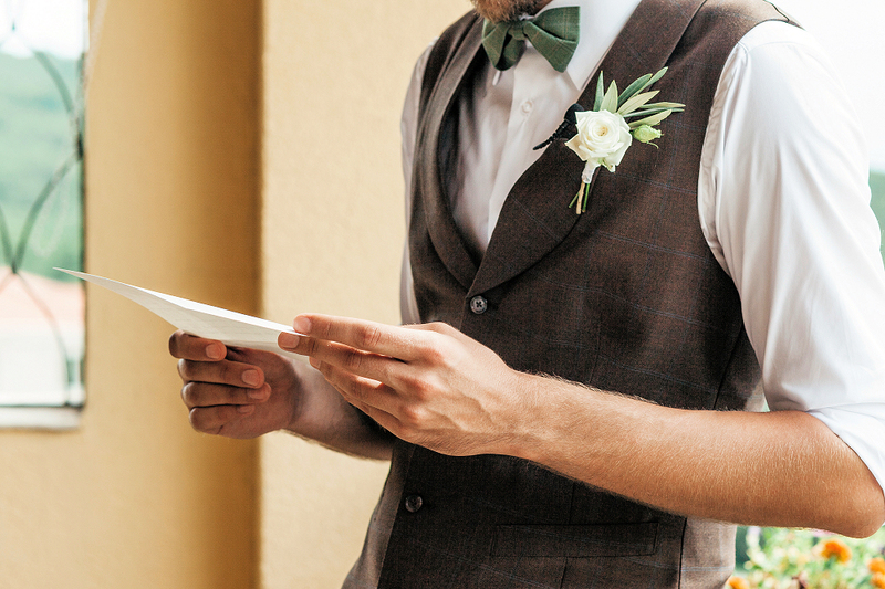 image of groom holding a wedding ceremony script, wedding traditions and planning