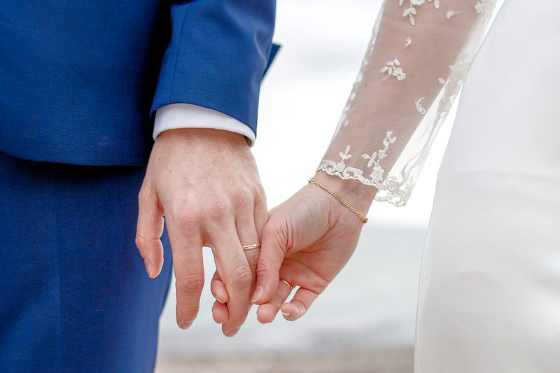 a bride and groom holding hands, this image shows the torso and hands only, with the groom in a blue suit and the woman in a dress with a lace white sleeve