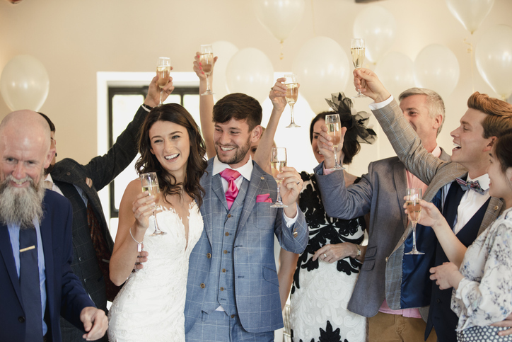 photograph of a happy couple at their wedding reception, surrounded by toasting friends and family after the ceremony, balloons and champagne and smiling