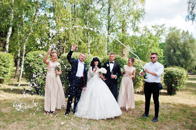 a happy group celebrate a group wedding elopement outdoors with a toast of champagne and laughter