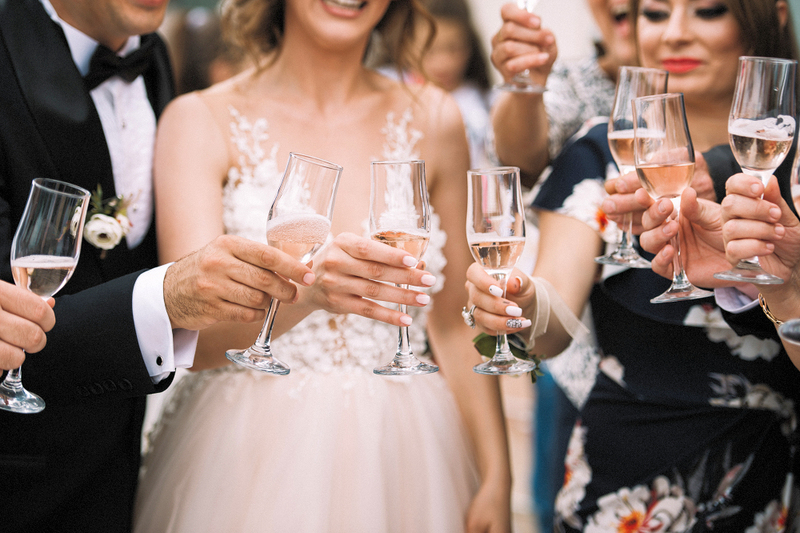 couple celebrates their wedding with a toast of champagne outside with their friends during a group wedding ceremony