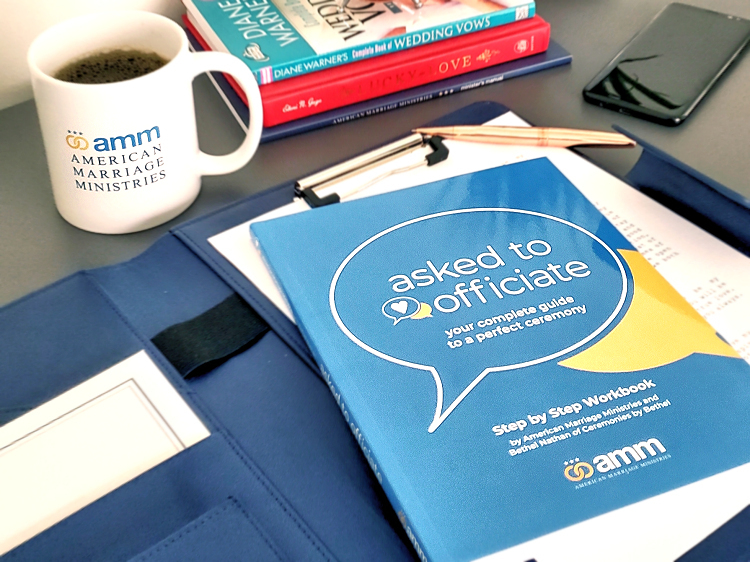 Image is a photograph of an American Marriage Ministries mug with coffee, on a desk next to a copy of Asked to Officiate, a complete guide to writing and delivering a wedding ceremony