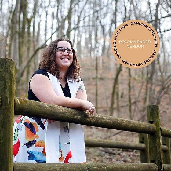 AMM Minister Maria Michonski, MDiv., stands leaning against a wooden railing, outside in the woods in a brightly patterned skirt smiling, taken from Pride of Place website