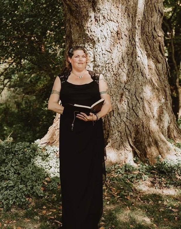 image is a photograph of Reverend Scarlett standing in front of an old tree filled with dark green leaves, Scarlett is wearing a long black dress and smiling, holding a small book, with tattoos on her arms and her curly hair pulled back in barrettes, posing before a wedding ceremony