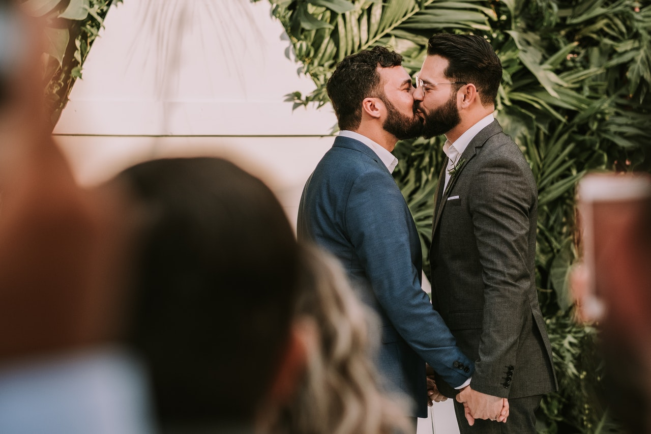 Men wearing suit kissing in front of people 3491999