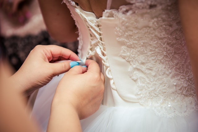 Photo of woman fixing the wedding gown 1021731