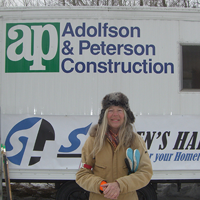 Woman in hat and jacket standing in front of AP Construction sign