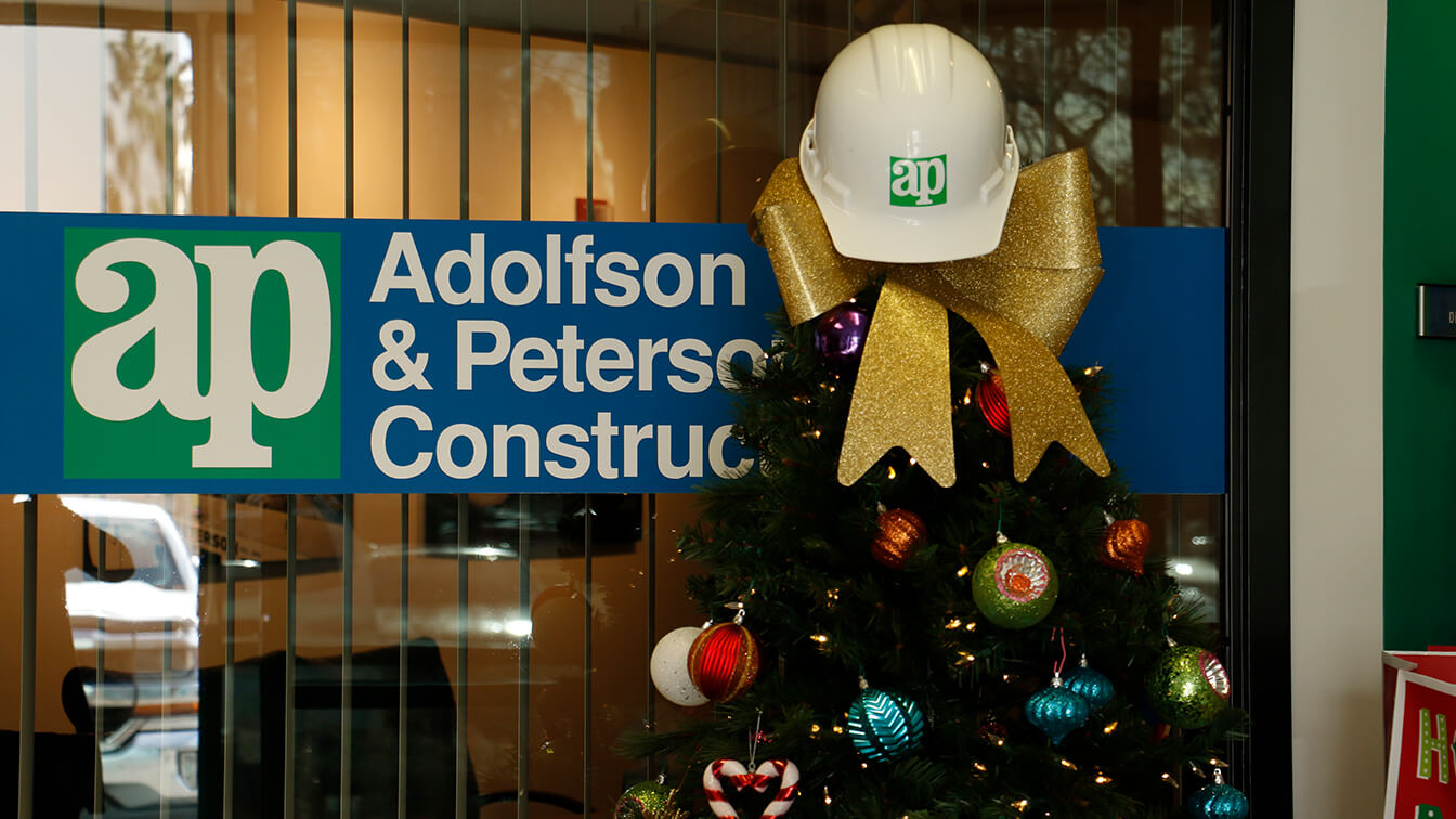 christmas tree with hard hat topper in front of company logo