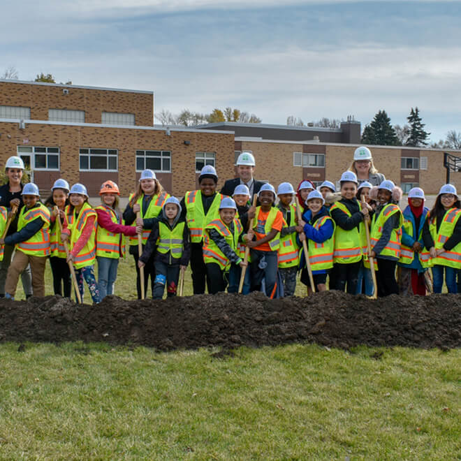 Group of kids breaking ground in front of building