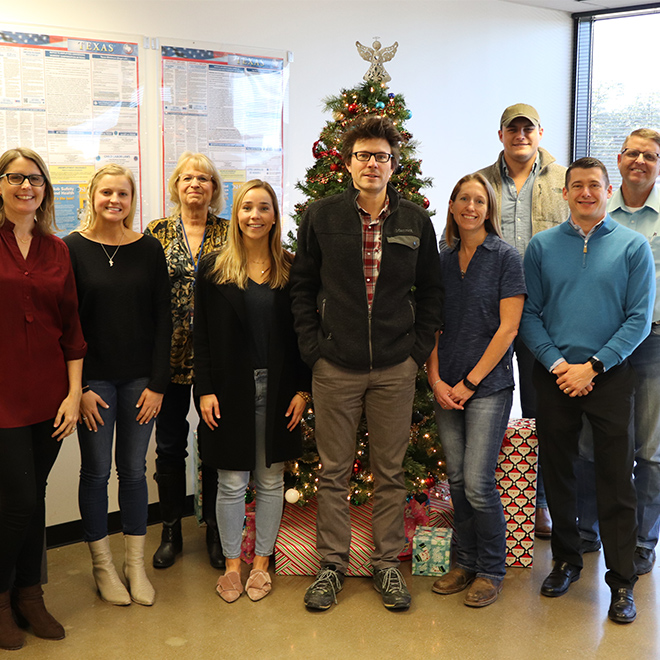 Nine people standing in front of christmas tree
