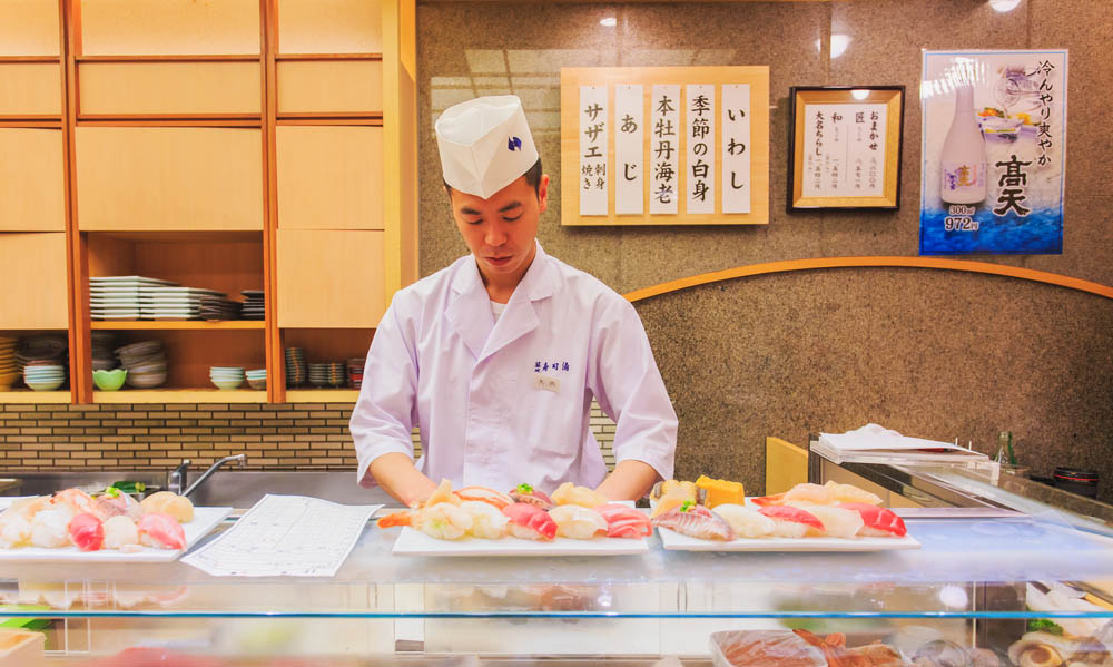 A chef preparing sushi at Tsukiji Outer Market sushi bar.