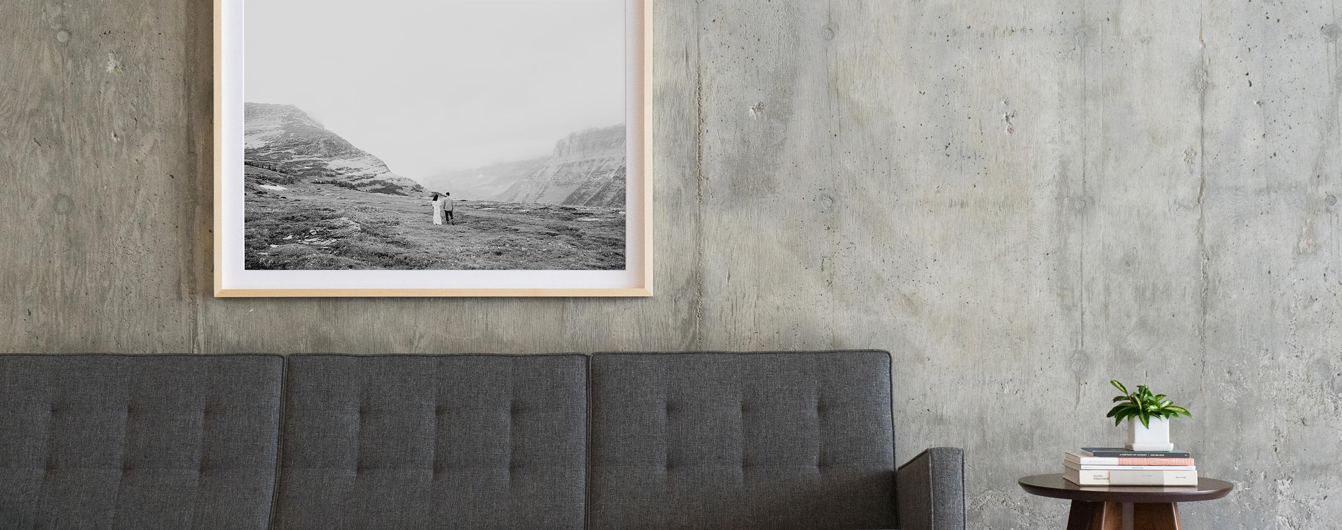 Black and white wall art hanging above a grey couch in a modern space