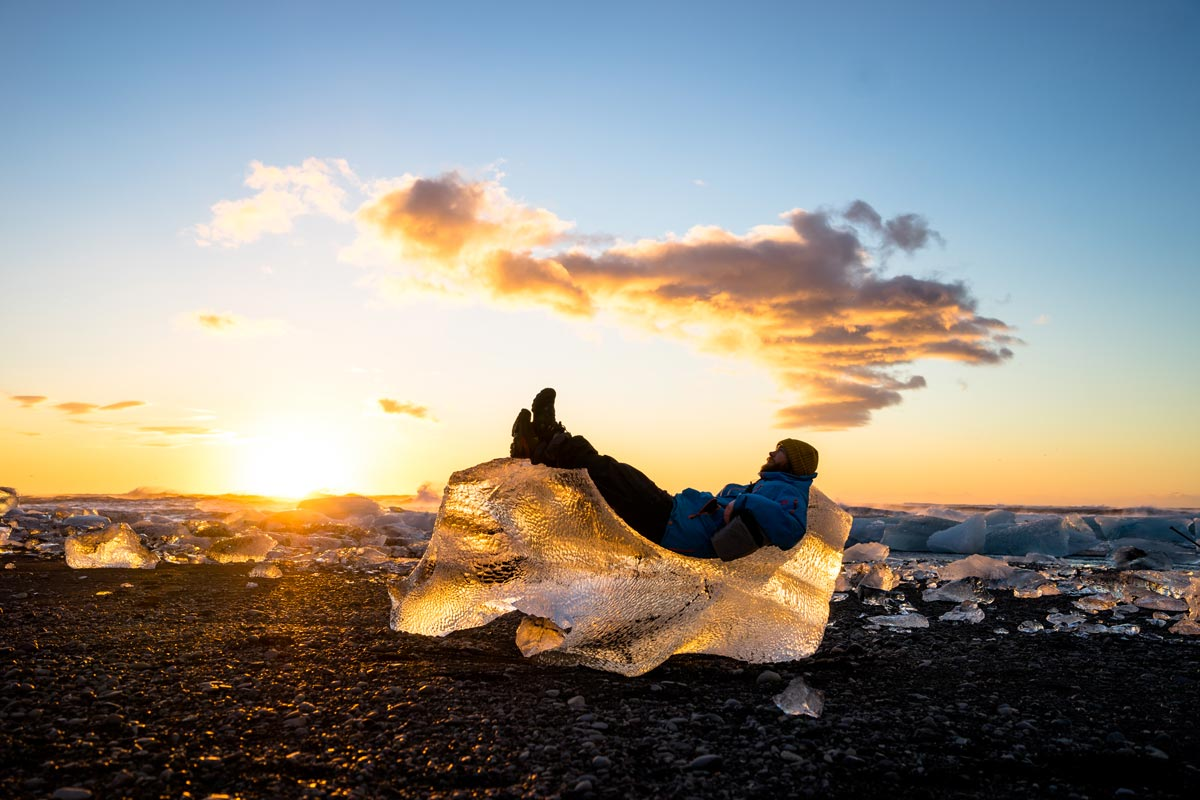 Chris Burkard photo of man laying on large chunk of ice at golden hour