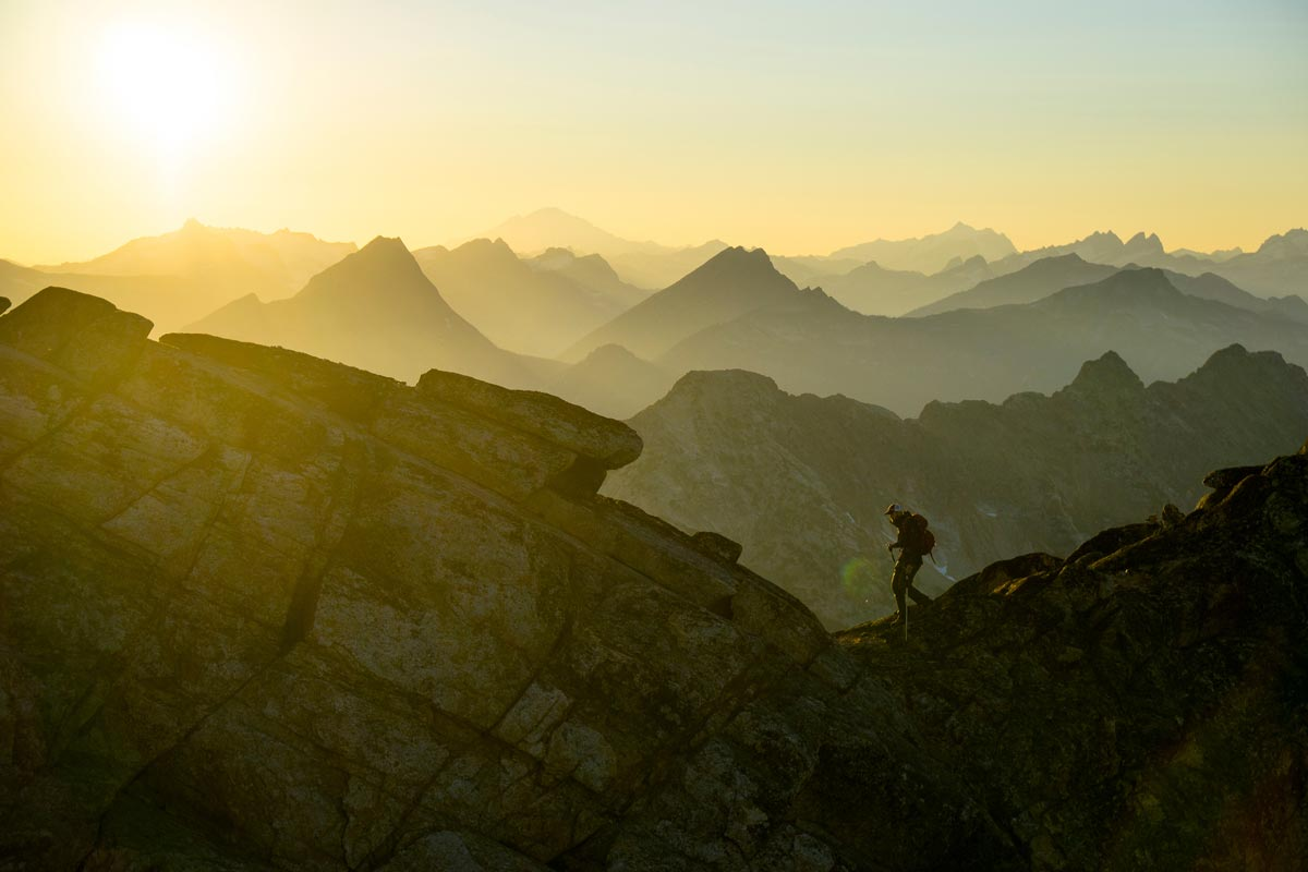 Chris Burkard photo of man hiking across saddle between mountain summits at golden hour