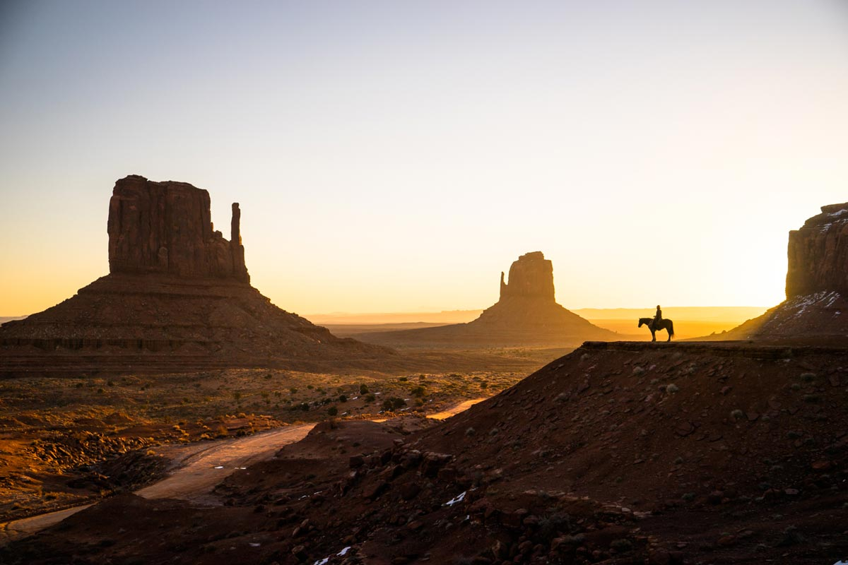 Silhouette of man on horse next to unique desert rock formations