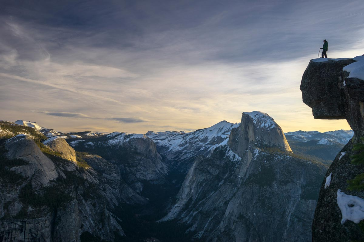 Chris Burkard photo of man standing at edge of rock atop a mountain looking into mountain range